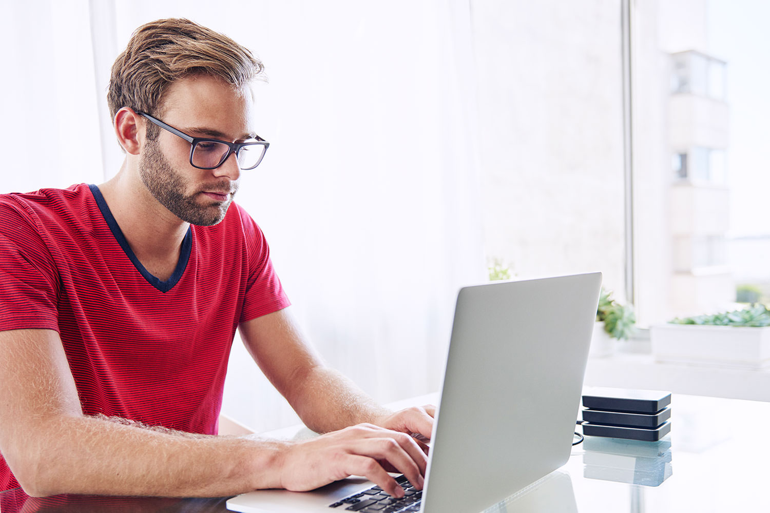 Man in red shirt typing on a laptop.