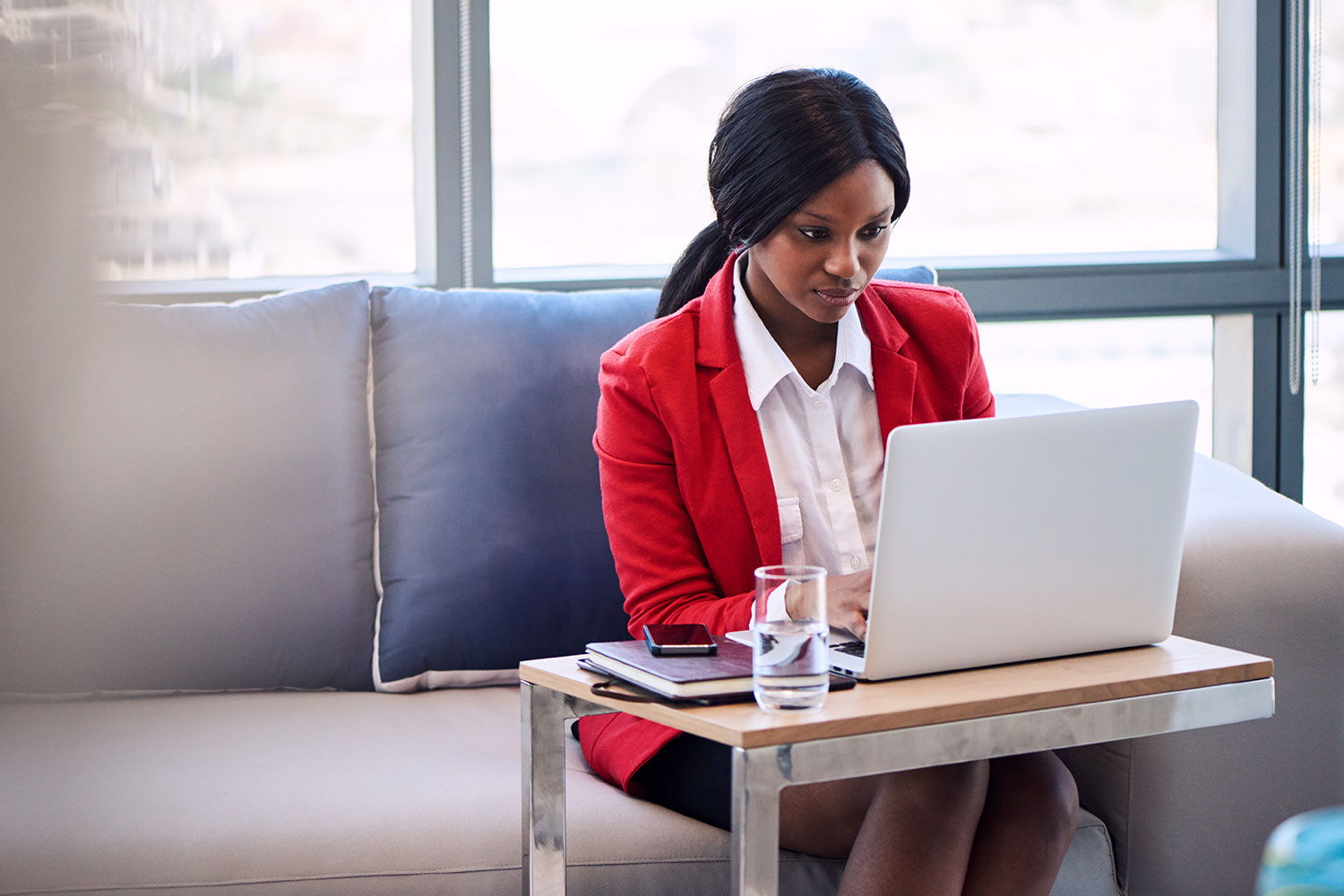 Woman in red jacket on laptop.