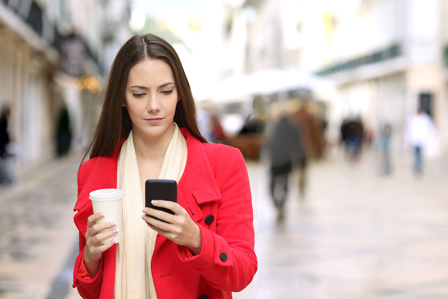 Woman in red with cell phone and coffee.