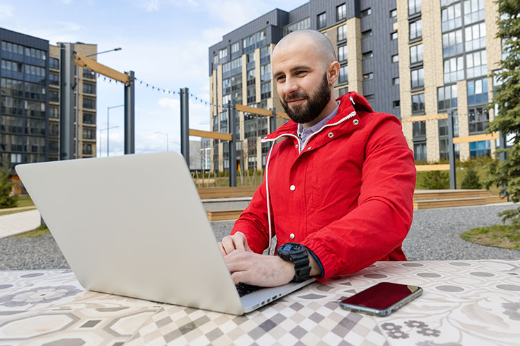 Man in red jacket using laptop outdoors.