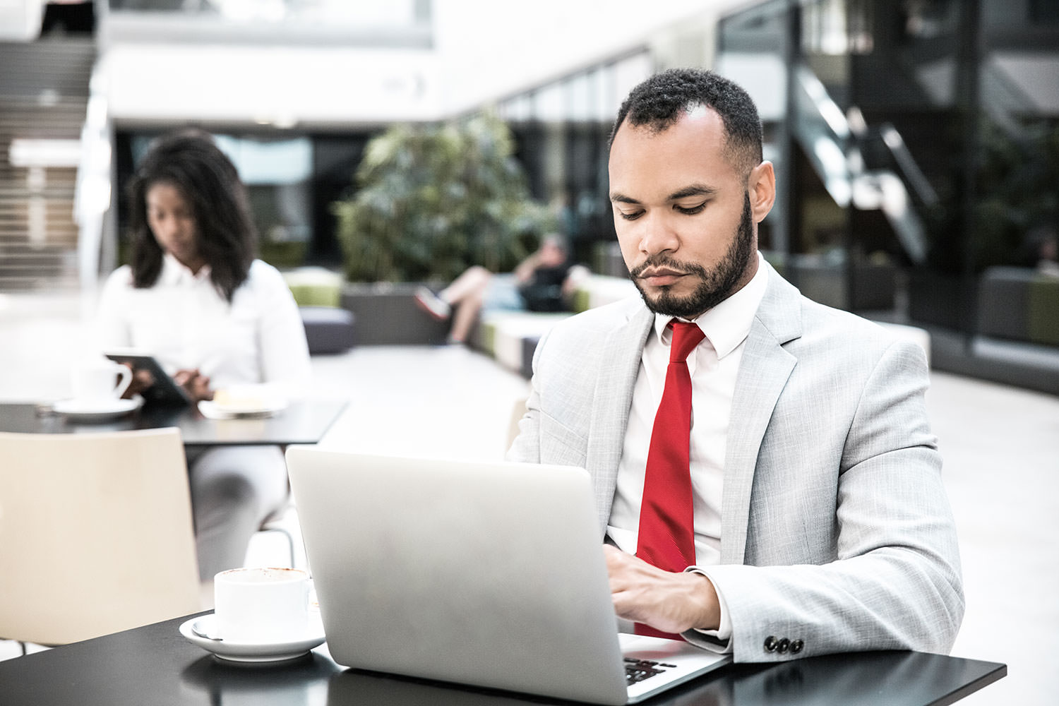 Man with red tie on a laptop.