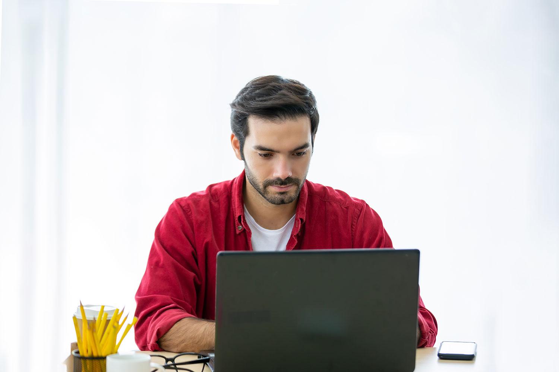 Man in red shirt using laptop.
